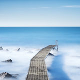 Pier or jetty on a blue ocean in the morning. Long Exposure Stock Photos