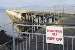 Pier Jetty Derelict Rotten Wooden perigoso evita o sinal pela praia do mar foto de stock