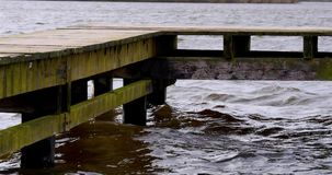 Pier or jetty in lake during storm. Pier or jetty in a natural lake on a stormy morning in The Neherlands stock video footage