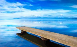 Pier or jetty, sunset blue panoramic landscape. Orbetello lagoon. With reflection, Argentario, Tuscany, Italy Royalty Free Stock Photos
