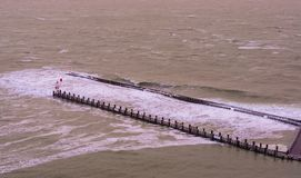 The pier jetty of vlissingen with wooden poles and small lighthouse, wild sea with waves at high tide, Zeeland, The Netherlands stock photos