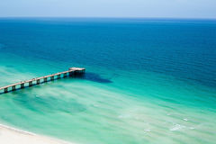 Pier jutting out from beach to sea in graduated shades of blue and green under clear skies. Royalty Free Stock Photo