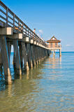Pier jutting out into the Gulf of mexico. Wood and concrete fishing pier with visitors, jutting out into the calm, tropical waters of Gulf of Mexico  on a sunny Stock Images