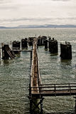 Pier on Lake. Pier floating on a river surrounded by a cloudy sky and mountains Royalty Free Stock Photo
