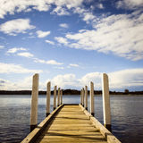 Pier on the lake. An old wooden pier on a calm, serene lake Stock Photos