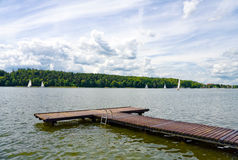 Pier on lake. Empty wooden pier on a Masurian lake,sailing boats and forest. Blue cloudy sky Royalty Free Stock Images