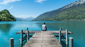 The Pier into the lake Brienzersee in village of Iseltwald Switzerland. Iseltwald, Switzerland, May 2017: The Pier into the lake Brienzersee in village of Stock Image