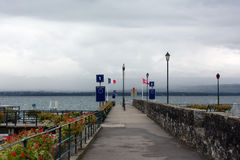 Pier on the lake with flags of Switzerland and France Stock Photos