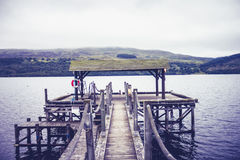 Pier at lake on gloomy day Stock Images