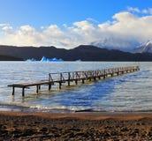 Pier on Lake Grey and blue iceberg Stock Photo