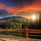 Pier on lake in pine forest at sunset Royalty Free Stock Image