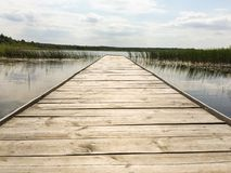Pier on a lake in Poland. Wooden pier on a wild lake in Europe Royalty Free Stock Images