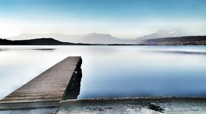 Pier on the lake in a relaxing day. Relaxing on the board of lake of Viverone royalty free stock photos