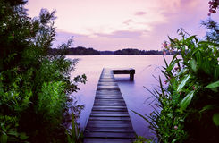 Pier in lake at sunrise Stock Images