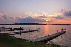 Pier in lake at sunset, Canada. Motorboat docked at wooden pier at sunset on lake in Canada Stock Photography