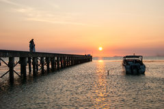 Pier landscape at sunset, people the going on a pier, happy people walking at the sea and observing a decline. Royalty Free Stock Photos