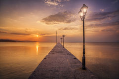 Pier with lanterns at sunset. In greece Stock Photo