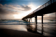Pier leading out to ocean Royalty Free Stock Image