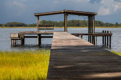 Pier leading to empty boathouse on lake. Wooden pier above grass leading to empty boathouse shelter structure with bench on water river lake intracoastal Stock Photos