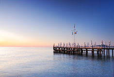 Pier lighted by sunrise glowing. Wooden pier lighted by sunrise glowing Stock Photos