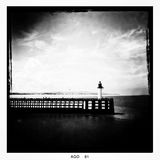 Pier with lighthouse. People walk on a wooden pier with lighthouse Royalty Free Stock Images