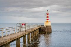 The Amble Pier Lighthouse, England, UK. The Pier Lighthouse in Amble in Northumberland, England, UK, seen from the South Pier stock photos