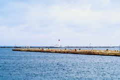 Pier and lighthouse on the background of the sea landscape. Odessa Sea Port. Closeup, copy space stock images