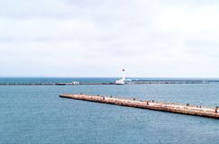 Pier and lighthouse on the background of the sea landscape. Odessa Sea Port. Closeup, copy space royalty free stock images