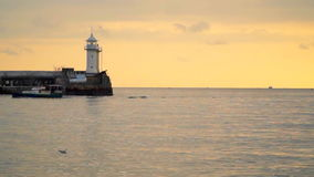 Pier with a lighthouse in the evening. The boat sails past stock video footage