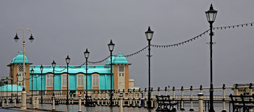 Pier lit up against grey sky Stock Photo