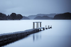 Pier on Loch Ard. Scenic view of pier on Loch Ard with silhouetted shoreline at dawn, Scotland royalty free stock photo