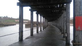 Looking Through Whitby Pier, North Yorkshire. Looking towards Whitby along the underside of the pier. Overcast, summer royalty free stock images