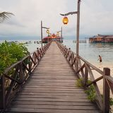 A pier on Mabul Island. Lit up by lanterns. Houses on water and dancing boy.  Overcast weather. Molo Royalty Free Stock Images