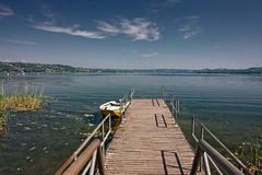 Pier met een boot op het meer op de lente wordt vastgelegd die royalty-vrije stock foto