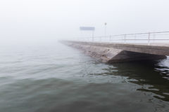 A pier in the midst of fog. A pier on a lake in the midst of fog royalty free stock images
