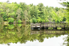 Pier at Mirror Lake State Park in Wisconsin. A pier with it`s reflection and lots of trees and their reflection on Mirror Lake State Park by Wisconsin Dells in Royalty Free Stock Photography