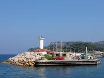 Pier mit einem Leuchtfeuer gegen das Meer und die Berge. Stockfotografie