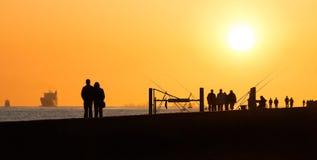 Pier mit Leutefischen und -c$gehen Stockfotos