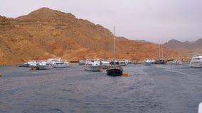 Pier mit Schiffen und Yachten auf dem Hintergrund von Bergen in der Wüste von Ägypten stock footage