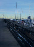 Pier at Monterey. This is a shot of the pier at Monterey, CA. There are sailboats along the pier Stock Image