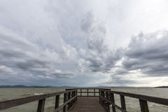 Pier and moody sky. Geometric, first person view of a pier on a lake, beneath an overcast, moody sky royalty free stock image