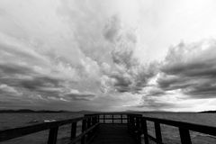 Pier and moody sky. Geometric, first person view of a pier on a lake, beneath an overcast, moody sky Royalty Free Stock Photography