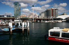 Pier with mooring posts, anchored boats, Pyrmont Bridge and city harbor waterfront with iconic cityscape in Sydney Darling Harbour stock images