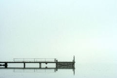 Pier in morning fog. Side view of a pier in morning fog. Pier extending out from lower left side of image with reflection in water. Misty atmosphere makes Royalty Free Stock Photography