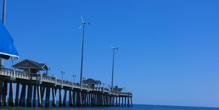 Pier on Nag`s Head beach, North Carolina. Beautiful sunny day and bright blue sea Royalty Free Stock Images
