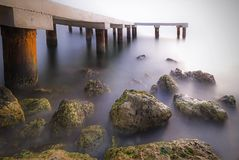 The pier is near the sea. It was shot as long exposure so there are a lot of rocks. Rocks has mosses. The sea looks as foggy royalty free stock photography