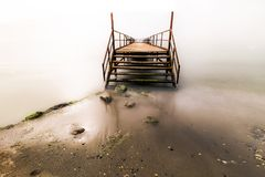 Pier in the light. Raised platform built from the shore out over sea, water, lake. You can fishing or swiming from here. The pier is near the sea. It was shot as royalty free stock image