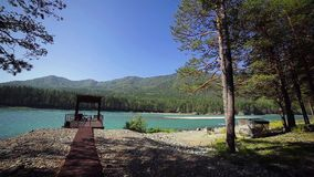Pier near the turquoise mountain river, trees. Wide angle stock video
