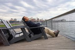 Pier 15. NEW YORK - MARCH 17, 2016: man sit in the armchair at Pier 15 at daytime. Pier 15 is located east of South Street and FDR Drive in Lower Manhattan, New Stock Photos