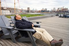 Pier 15. NEW YORK - MARCH 17, 2016: man sit in the armchair at Pier 15 at daytime. Pier 15 is located east of South Street and FDR Drive in Lower Manhattan, New Royalty Free Stock Photo